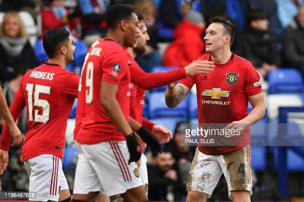 Manchester United's English defender Phil Jones celebrates with teammates after scoring their fourth goal during the English FA Cup fourth round...