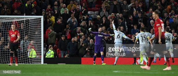 Manchester United's English defender Phil Jones leaves the pitch after Derby's English goalkeeper Scott Carson saved his penalty during the English...