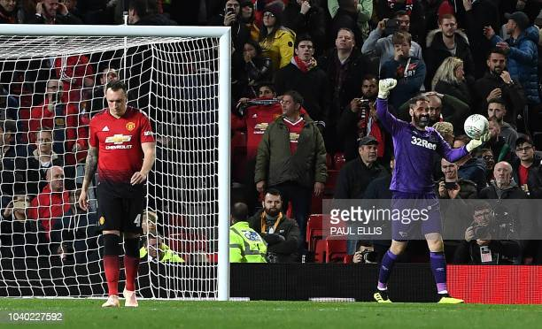 TOPSHOT Manchester United's English defender Phil Jones leaves the pitch after Derby's English goalkeeper Scott Carson saved his penalty during the...