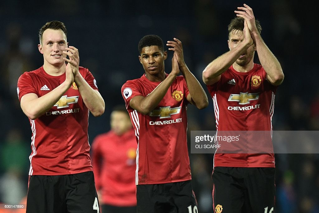 Manchester United's English defender Phil Jones (L), Manchester United's English striker Marcus Rashford (C) and Manchester United's English midfielder Michael Carrick (R) celebrate on the pitch after the English Premier League football match between West Bromwich Albion and Manchester United at The Hawthorns stadium in West Bromwich, central England, on December 17, 2016. Manchester United won the game 2-0. / AFP / Oli SCARFF / RESTRICTED TO EDITORIAL USE. No use with unauthorized audio, video, data, fixture lists, club/league logos or 'live' services. Online in-match use limited to 75 images, no video emulation. No use in betting, games or single club/league/player publications. /