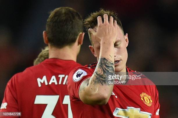 Manchester United's English defender Phil Jones reacts after being caught by Tottenham Hotspur's Brazilian midfielder Lucas Moura with a high boot...