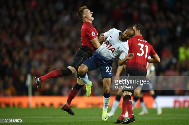 Manchester United's English defender Phil Jones reacts after Tottenham Hotspur's Brazilian midfielder Lucas Moura caught him with a high boot earning...
