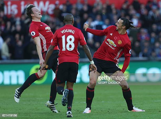 Manchester United's English defender Phil Jones reacts after Manchester United's Swedish striker Zlatan Ibrahimovic kicked the air as he celebrated...