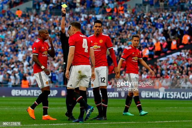 Manchester United's English defender Phil Jones receives a yellow card during the English FA Cup final football match between Chelsea and Manchester...