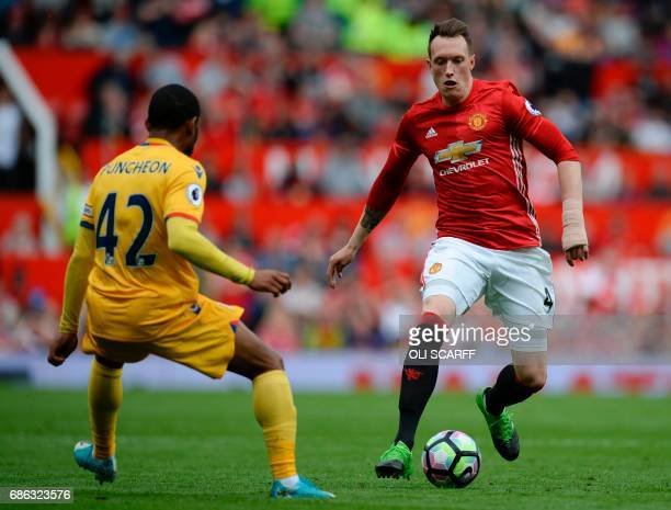 Manchester United's English defender Phil Jones runs at Crystal Palace's English midfielder Jason Puncheon during the English Premier League football...