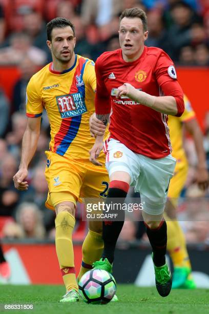 Manchester United's English defender Phil Jones runs with the ball chased by Crystal Palace's English defender Joel Ward during the English Premier...