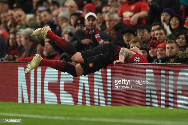 Manchester United's English defender Phil Jones trips over the advertising boards during the UEFA Champions League group H football match between...