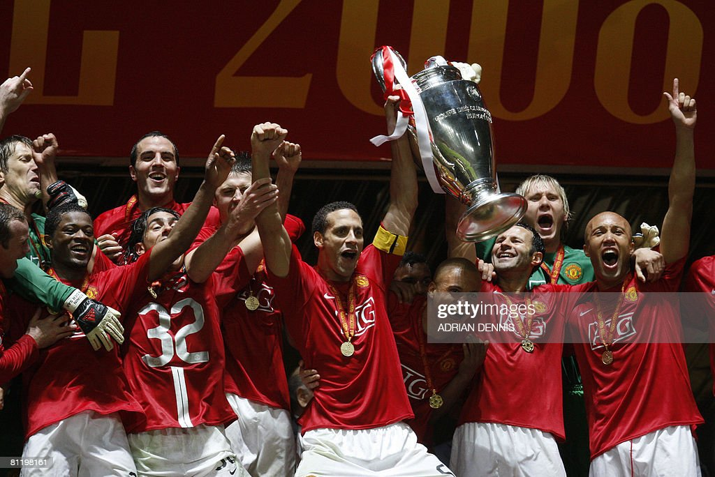 Manchester United's English defender Rio Ferdinand (C) holds up the trophy after beating Chelsea in the final of the Champions League football match at the Luzhniki stadium in Moscow on May 21, 2008. The match remained at a 1-1 draw and Manchester won on penalties after extra time. AFP PHOTO / Adrian Dennis