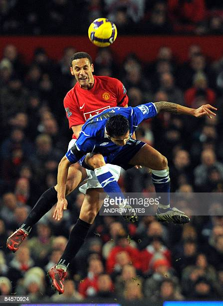 Manchester United's English defender Rio Ferdinand wins a header from Everton's Australian midfielder Tim Cahill during the English Premiership...