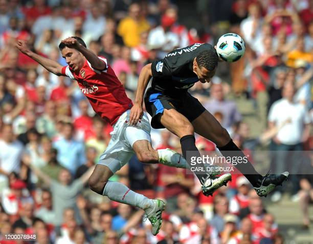 Manchester United's English defender Rio Ferdinand wins a header in front of Arsenal's Dutch striker Robin Van Persie during the English Premier...