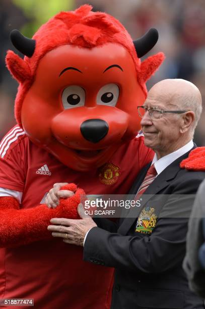 Manchester United's English former player Bobby Charlton shakes hands with the Red Devil mascot before the English Premier League football match...