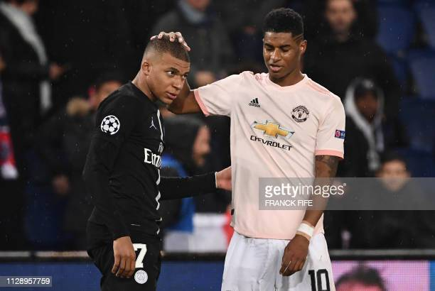 Manchester United's English forward Marcus Rashford cheers up Paris Saint-Germain's French forward Kylian Mbappe at the end of the UEFA Champions...