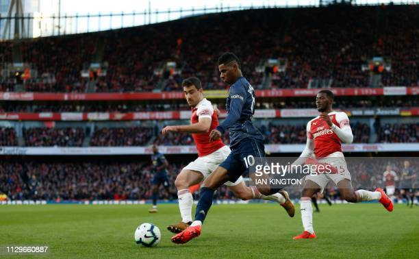 Manchester United's English forward Marcus Rashford takes on Arsenal's Greek defender Sokratis Papastathopoulos during the English Premier League...