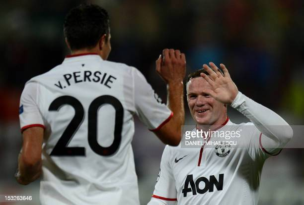 Manchester United's English forward Wayne Rooney celebrates with Manchester United's Dutch forward Robin van Persie after Persie scored during the...