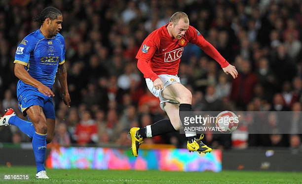 Manchester United's English forward Wayne Rooney controls the ball in front of Portsmouth's English defender Glen Johnson during the English...
