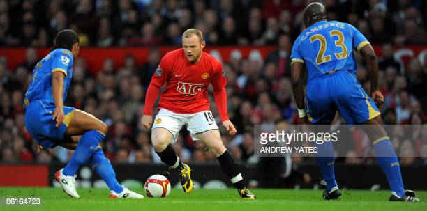 Manchester United's English forward Wayne Rooney vies with Portsmouth's English defender Sol Campbell and Portsmouth's English defender Glen Johnson...