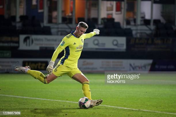 Manchester United's English goalkeeper Dean Henderson takes a goal kick during the English League Cup third round football match between Luton Town...