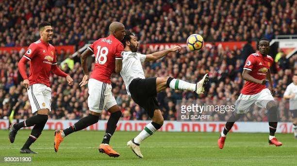 Manchester United's English midfielder Ashley Young challenges Liverpool's Egyptian midfielder Mohamed Salah during the English Premier League...