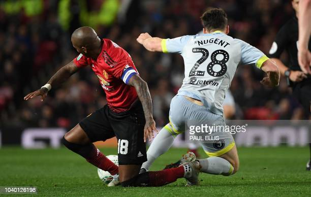 Manchester United's English midfielder Ashley Young fouls Derby's English striker David Nugent during the English League Cup third round football...