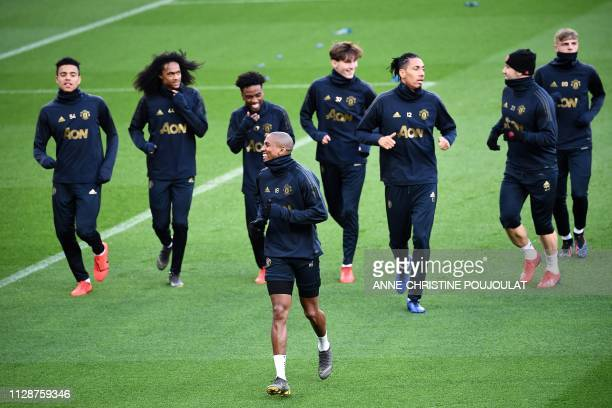 Manchester United's English midfielder Ashley Young jogs ahead of teammates during a training session at The Parc des Princes stadium in Paris on...