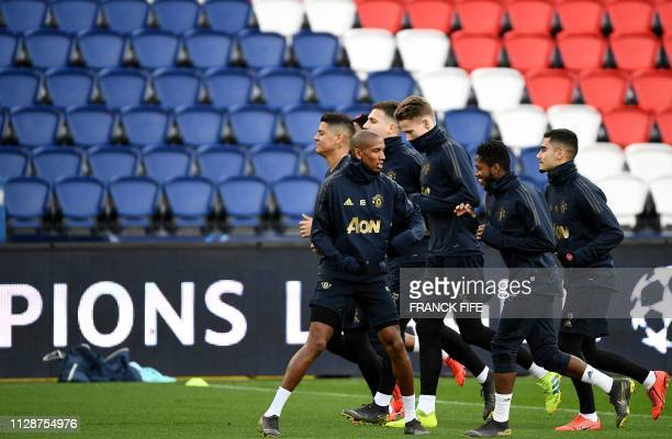 Manchester United's English midfielder Ashley Young jokes with teammates during a training session at The Parc des Princes stadium in Paris on March...