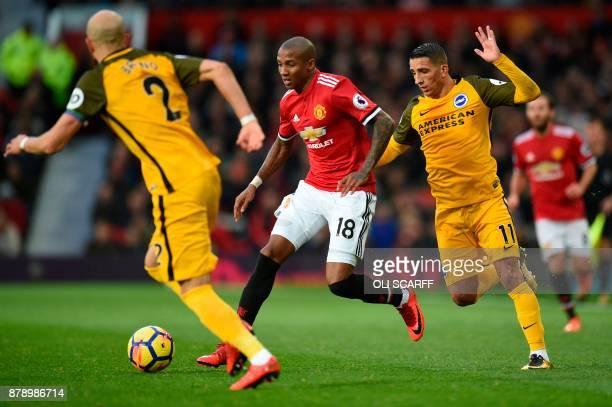 Manchester United's English midfielder Ashley Young takes on Brighton's Spanish defender Bruno Saltor and Brighton's French midfielder Anthony...