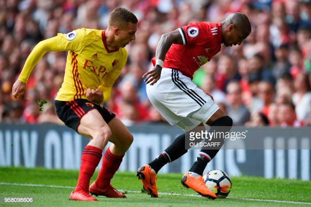 Manchester United's English midfielder Ashley Young tries to hold off Watford's Spanish midfielder Gerard Deulofeu during the English Premier League...