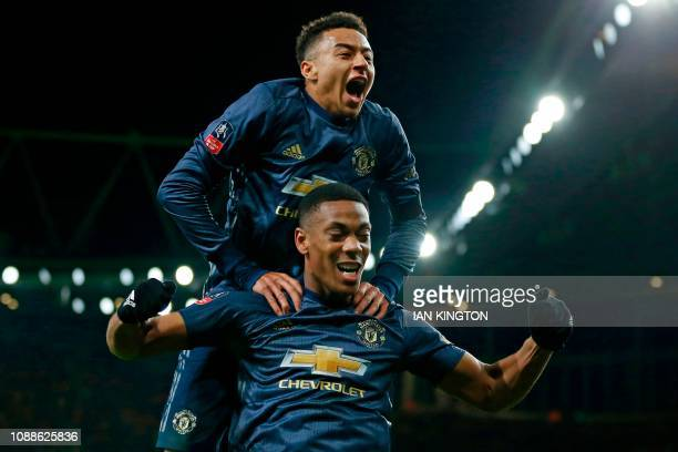 Manchester United's English midfielder Jesse Lingard celebrates by leaping onto the back of Manchester United's French striker Anthony Martial after...