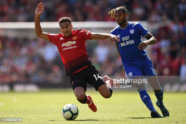 Manchester United's English midfielder Jesse Lingard falls under pressure from Cardiff City's Dutchborn Caracao midfielder Leandro Bacuna during the...