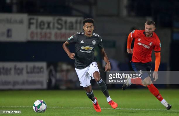 Manchester United's English midfielder Jesse Lingard runs with the ball chased by Luton Town's English midfielder Ryan Tunnicliffe during the English...