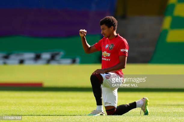 Manchester United's English midfielder Jesse Lingard takes a knee to show solidarity with the Black Lives Matter movement and to protest racism ahead...
