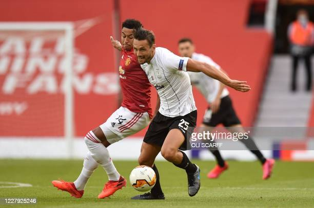 Manchester United's English midfielder Jesse Lingard vies with LASK's Australian midfielder James Holland during the UEFA Europa League last 16...