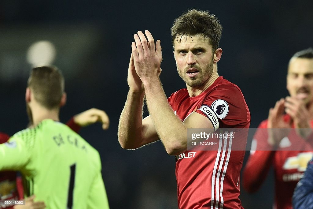 Manchester United's English midfielder Michael Carrick celebrates on the pitch after the English Premier League football match between West Bromwich Albion and Manchester United at The Hawthorns stadium in West Bromwich, central England, on December 17, 2016. Manchester United won the game 2-0. / AFP / Oli SCARFF / RESTRICTED TO EDITORIAL USE. No use with unauthorized audio, video, data, fixture lists, club/league logos or 'live' services. Online in-match use limited to 75 images, no video emulation. No use in betting, games or single club/league/player publications. /
