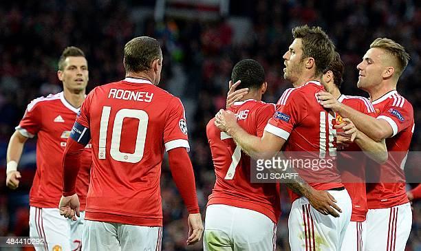 Manchester United's English midfielder Michael Carrick congratulates Manchester United's Dutch midfielder Memphis Depay after Depay scored his team's...