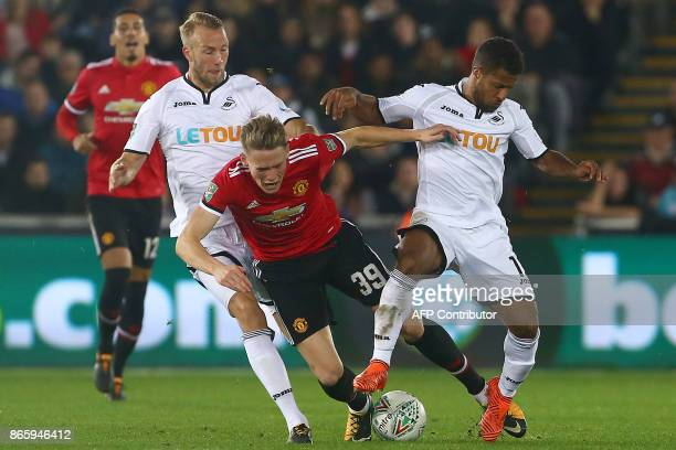 Manchester United's English midfielder Scott McTominay is tackled by Swansea City's Dutch defender Mike van der Hoorn and Swansea City's English...
