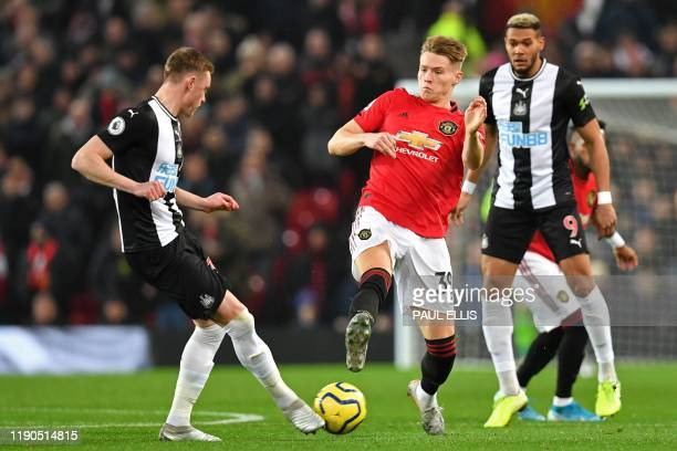 Manchester United's English midfielder Scott McTominay receives a yellow card for this challenge on Newcastle United's English midfielder Sean...