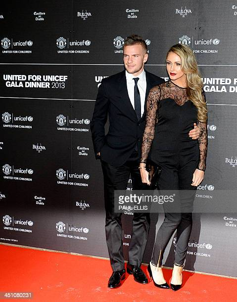 Manchester United's English midfielder Tom Cleverley and partner Georgina Dorsett pose for photographs as they arrive for a gala dinner in aid of...