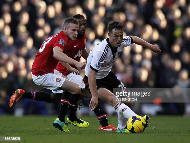 Manchester United's English midfielder Tom Cleverley vies with Fulham's English midfielder Scott Parker during the English Premier League football...