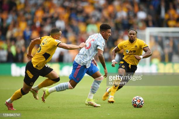 Manchester United's English striker Jadon Sancho is challenged by Wolverhampton Wanderers' Brazilian defender Marcal and Wolverhampton Wanderers'...