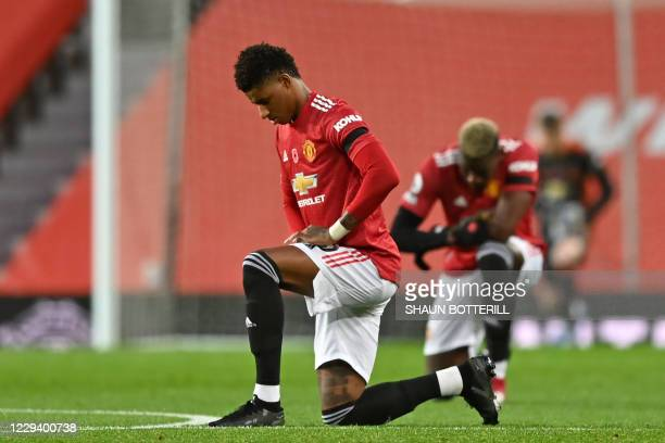 Manchester United's English striker Marcus Rashford and Manchester United's French midfielder Paul Pogba 'take a knee' in support of the No Room For...