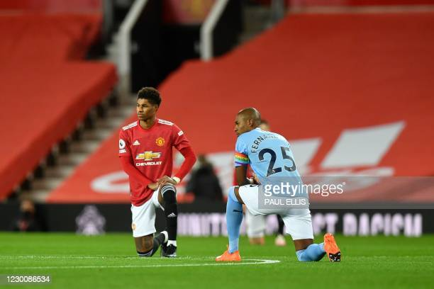Manchester United's English striker Marcus Rashford and Manchester City's Brazilian midfielder Fernandinho 'take a knee' in support of the No Room...
