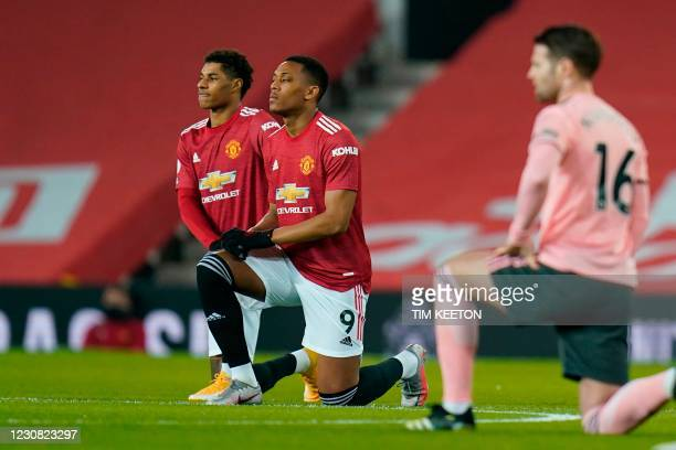 Manchester United's English striker Marcus Rashford and Manchester United's French striker Anthony Martial take a knee against racism during the...