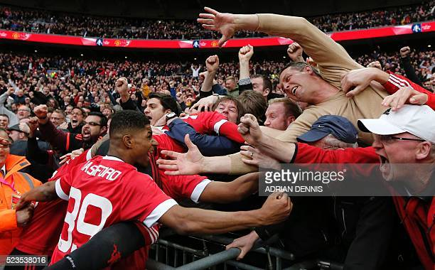 Manchester United's English striker Marcus Rashford and Manchester United's English midfielder Jesse Lingard celebrate with the crowd after...