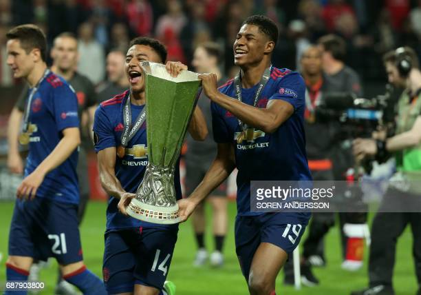 Manchester United's English striker Marcus Rashford and Manchester United's English midfielder Jesse Lingard celebrate with the trophy after their...