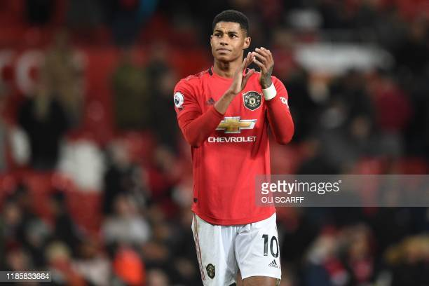 Manchester United's English striker Marcus Rashford applauds supporters on the pitch after the English Premier League football match between...