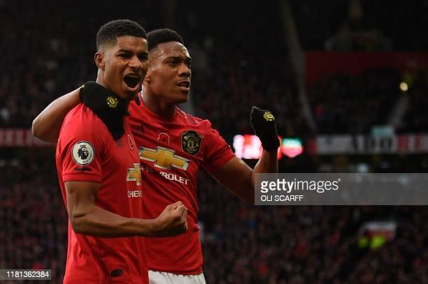 Manchester United's English striker Marcus Rashford celebrates scoring their third goal with Manchester United's French striker Anthony Martial...