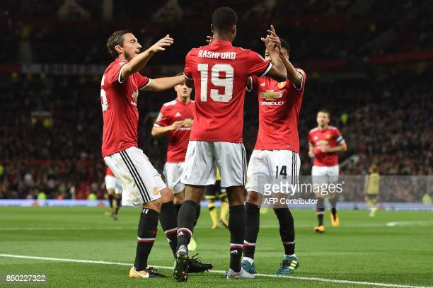 Manchester United's English striker Marcus Rashford celebrates scoring the opening goal with teammates during the English League Cup third round...