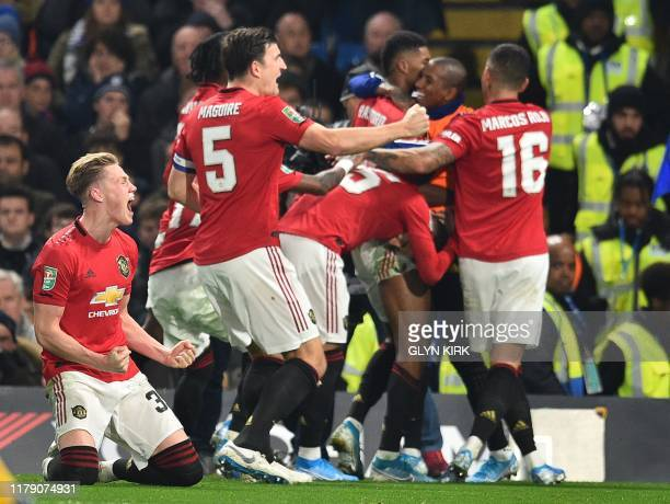Manchester United's English striker Marcus Rashford celebrates with teammates after he takes a penalty and scores his team's second goal during the...