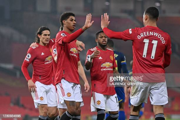 Manchester United's English striker Marcus Rashford celebrates with teammates after scoring their second goal during the English Premier League...