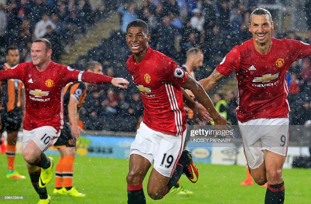 Manchester United's English striker Marcus Rashford (C) celebrates with Manchester United's Swedish striker Zlatan Ibrahimovic (R) and Manchester United's English striker Wayne Rooney (L) after scoring their late winning goal during the English Premier League football match between Hull City and Manchester United at the KCOM Stadium in Kingston upon Hull, north east England on August 27, 2016. Manchester united won the game 1-0. / AFP / Lindsey PARNABY / RESTRICTED TO EDITORIAL USE. No use with unauthorized audio, video, data, fixture lists, club/league logos or 'live' services. Online in-match use limited to 75 images, no video emulation. No use in betting, games or single club/league/player publications. /